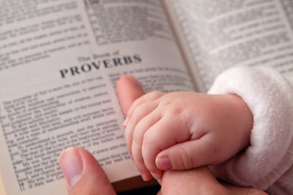 Baby Holding Dad's Finger on Bible; beauty is fleeting, but a woman who fears the Lord is to be praised