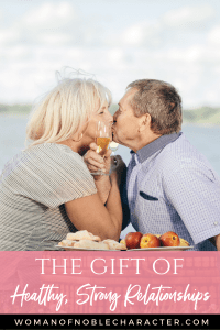 An older couple sitting on the shore kissing - the Gift of Healthy Strong Relationships