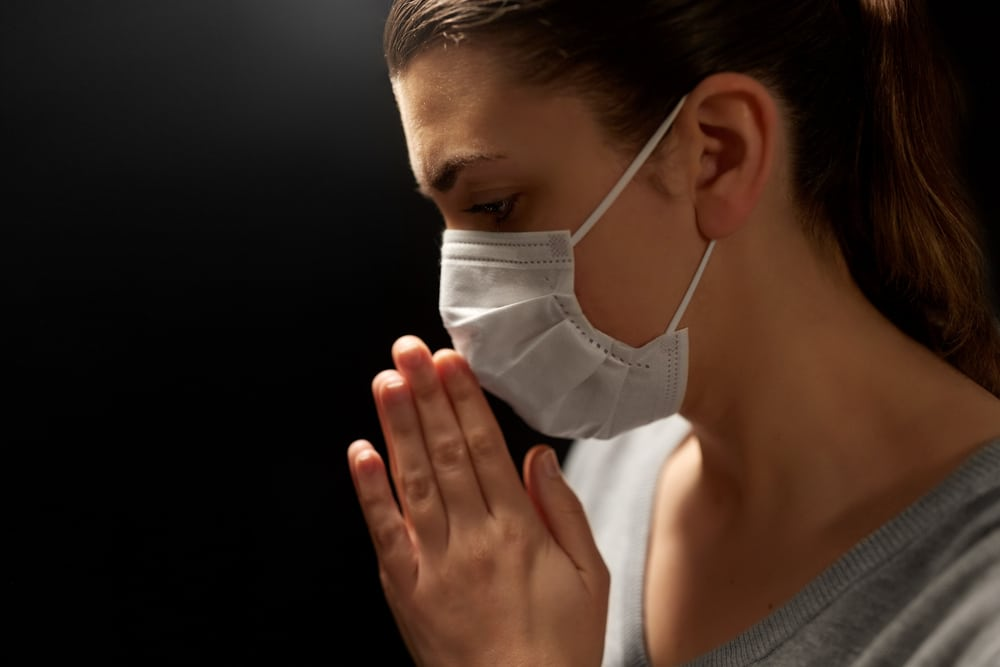 health protection, safety and pandemic concept - close up of sick young woman in protective medical face mask praying over black background;  people prayed for me and my cancer treatment