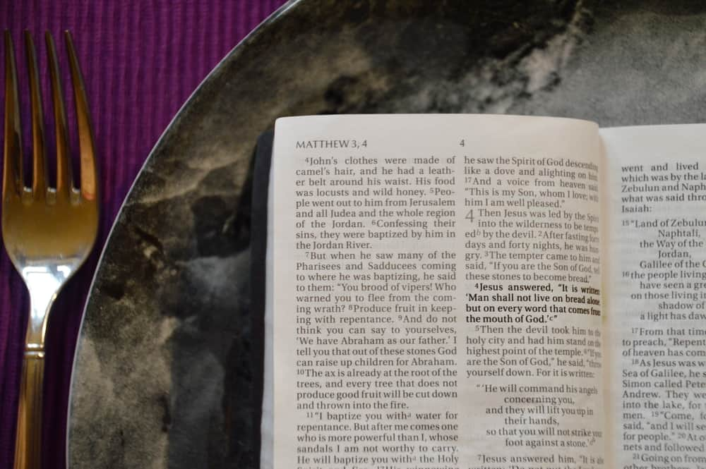 Bible on a dinner plate with silverware in lent, biblical fasting, growing closer to God