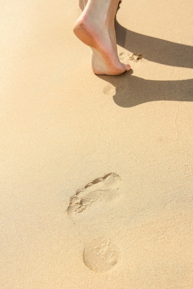 Beautiful footprints in the sand of the sea on a nature background; how to be closer to God