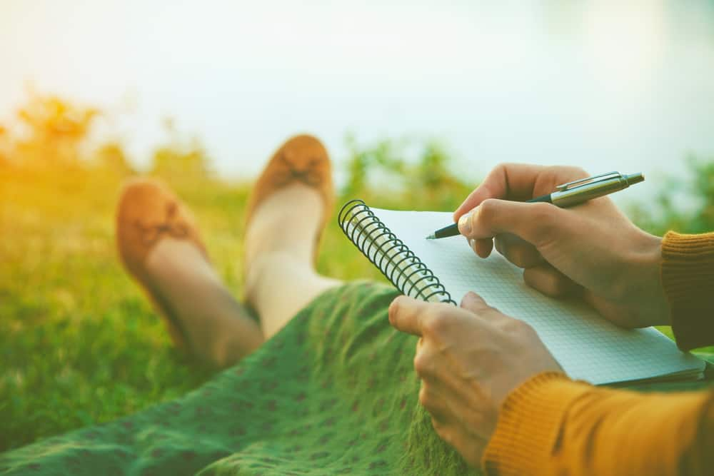 female hands with pen writing on notebook on grass outside; getting closer to God
