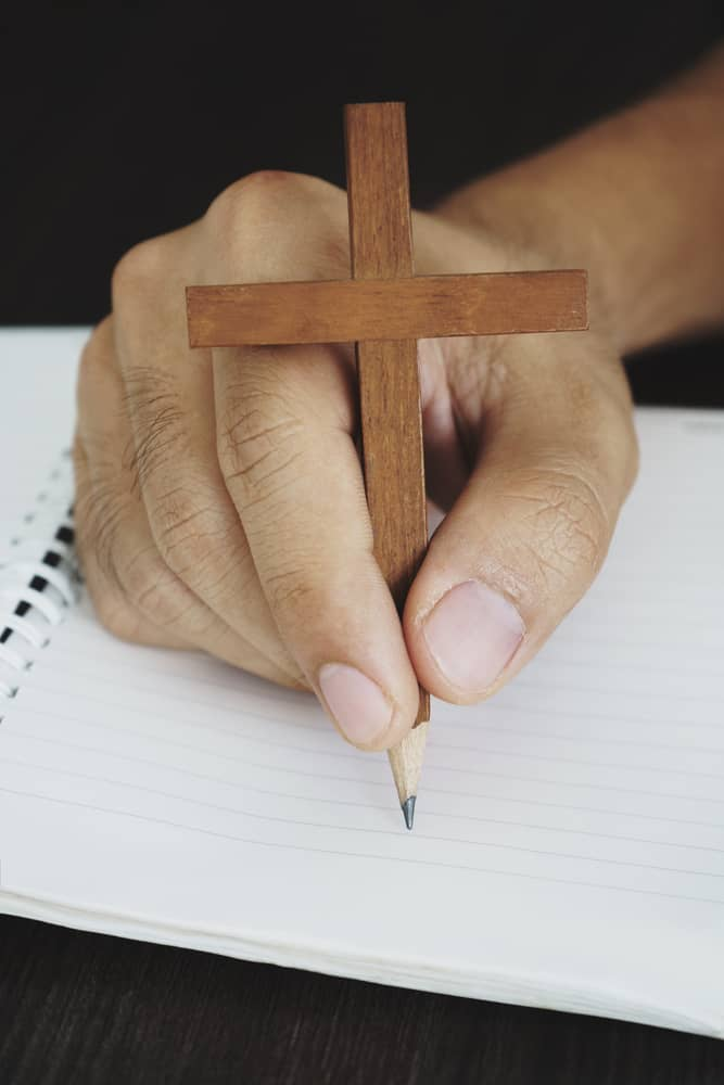 Surreal image of wooden cross pencil, prayer prompts