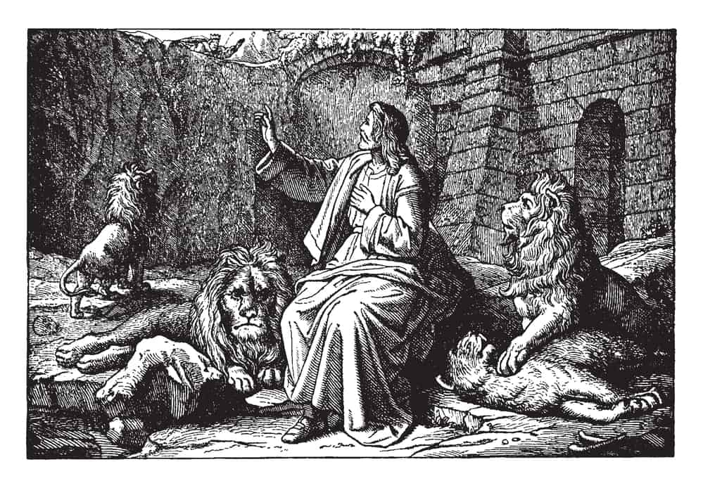 An ancient picture of Daniel sitting safely around the lions in the den. Daniel is looking up to the edge of the pit, where a king can be seen looking down on him, vintage line drawing or engraving illustration.; animals of the Bible