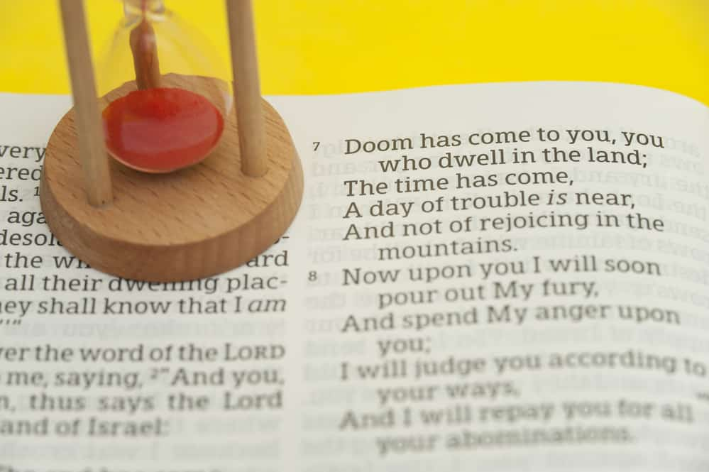 Hourglass on top of an open Holy Bible in the Book of the Prophet Ezekiel Chapter 7 highlighted in verse 7. Isolated on yellow background. Horizontal shot.; 7 in the Bible