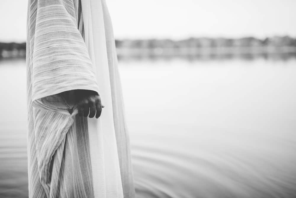 A closeup shot of a person wearing a biblical robe while standing in the water in black and white; symbolism of water in the Bible