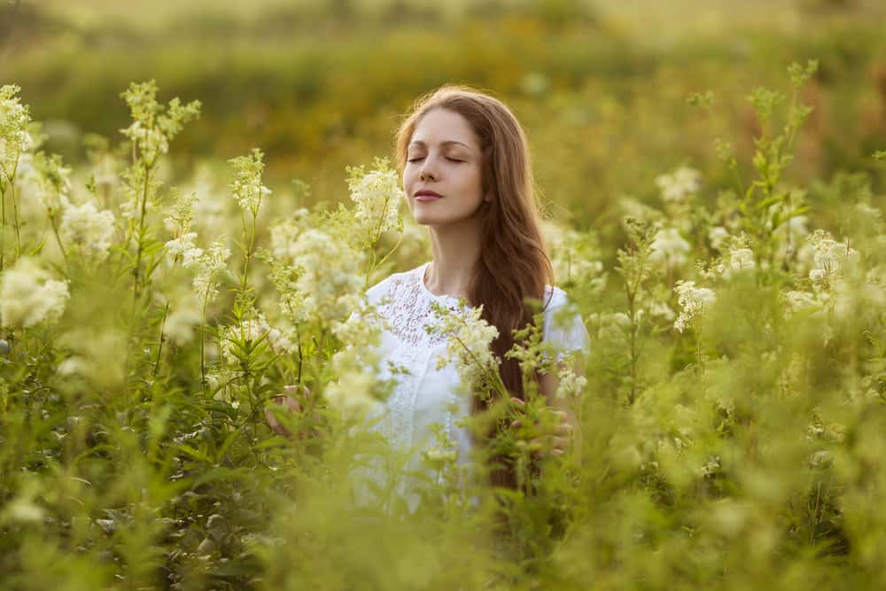 Happy young woman with eyes closed among the wildflowers; meek and gentle spirit