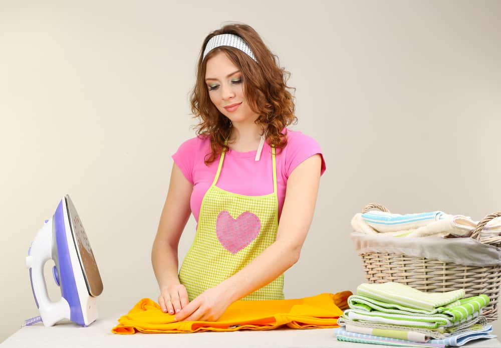Young beautiful woman ironing clothes in room on grey background for the post Holding the Distaff? What Proverbs 31:19 Really Means in Modern Society