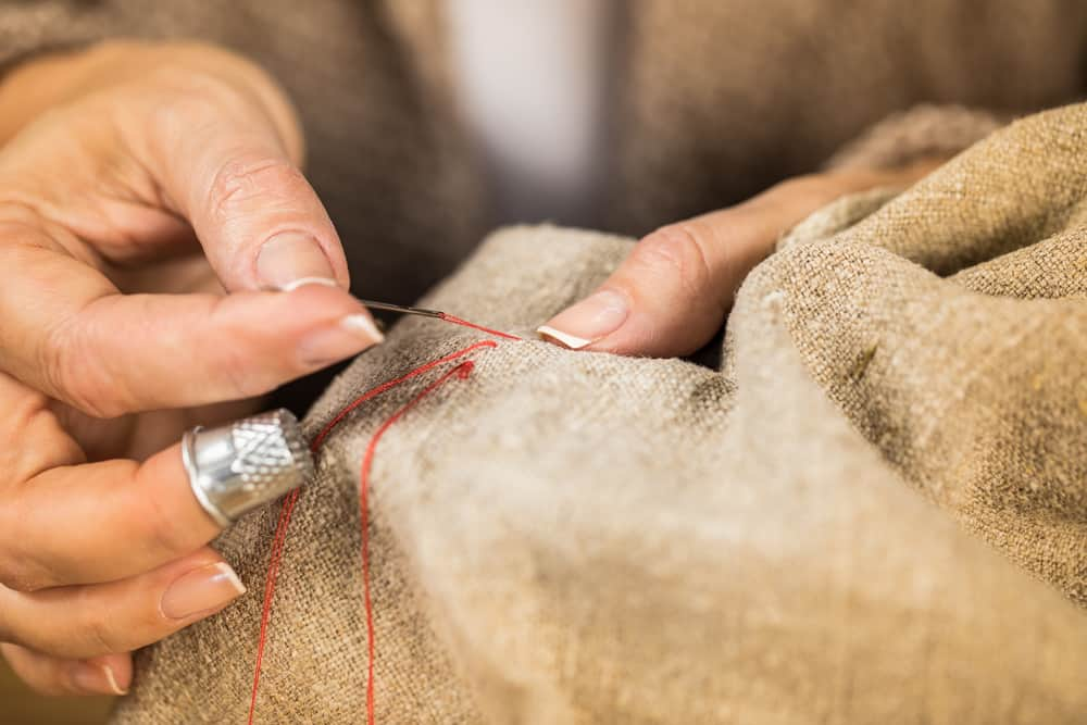 image of woman sewing burlap cloth with red thread for the post: